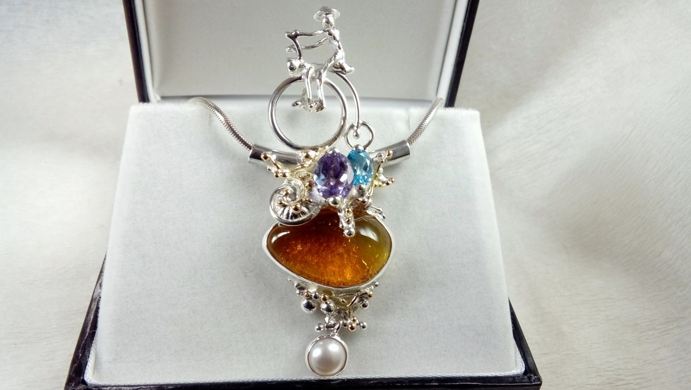 Gregory Pyra Piro artisan handcrafted bicycle pendant #1950, original handmade in sterling silver with solid 14 karat gold, facet cut blue topaz, facet cut amethyst, amber, pearl